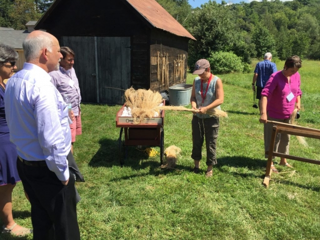 Photo of Michelle Parrish discussing how to process flax straw at the Flax & Linen Symposium 2016