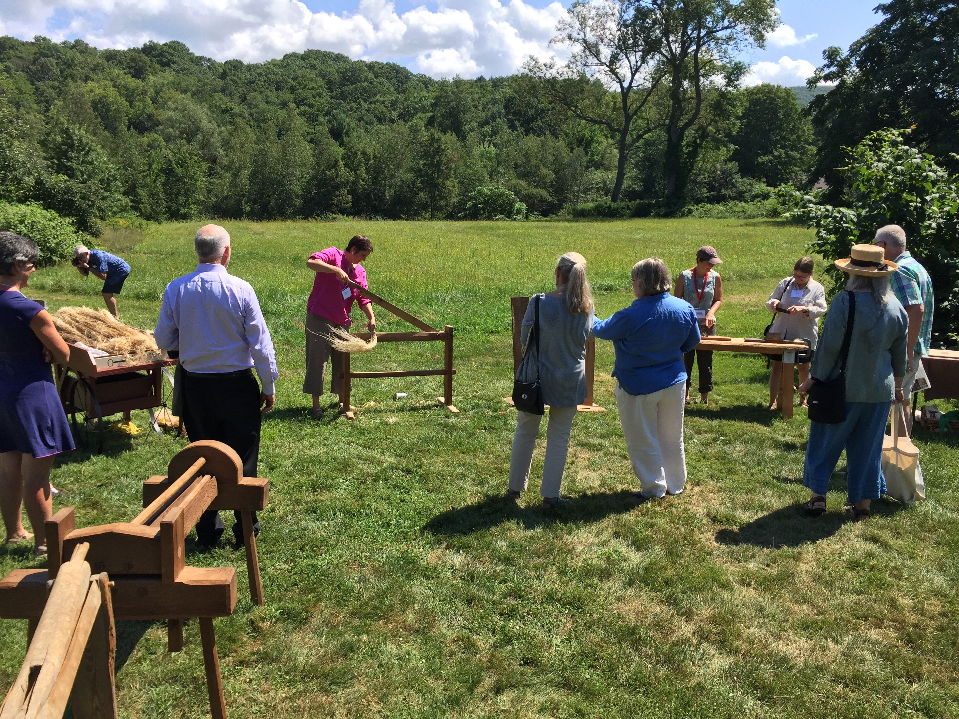 Photo of participants trying antique flax processing tools at the Flax & Linen Symposium 2016