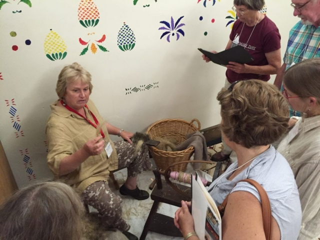Photo of Gina Gerhard demonstrating how to spin flax tow fiber at the Flax & Linen Symposium 2016