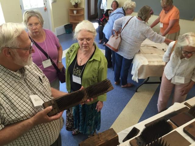 Photo of Ron Walter displaying his collection of antique flax hetchels at the Flax & Linen Symposium 2016