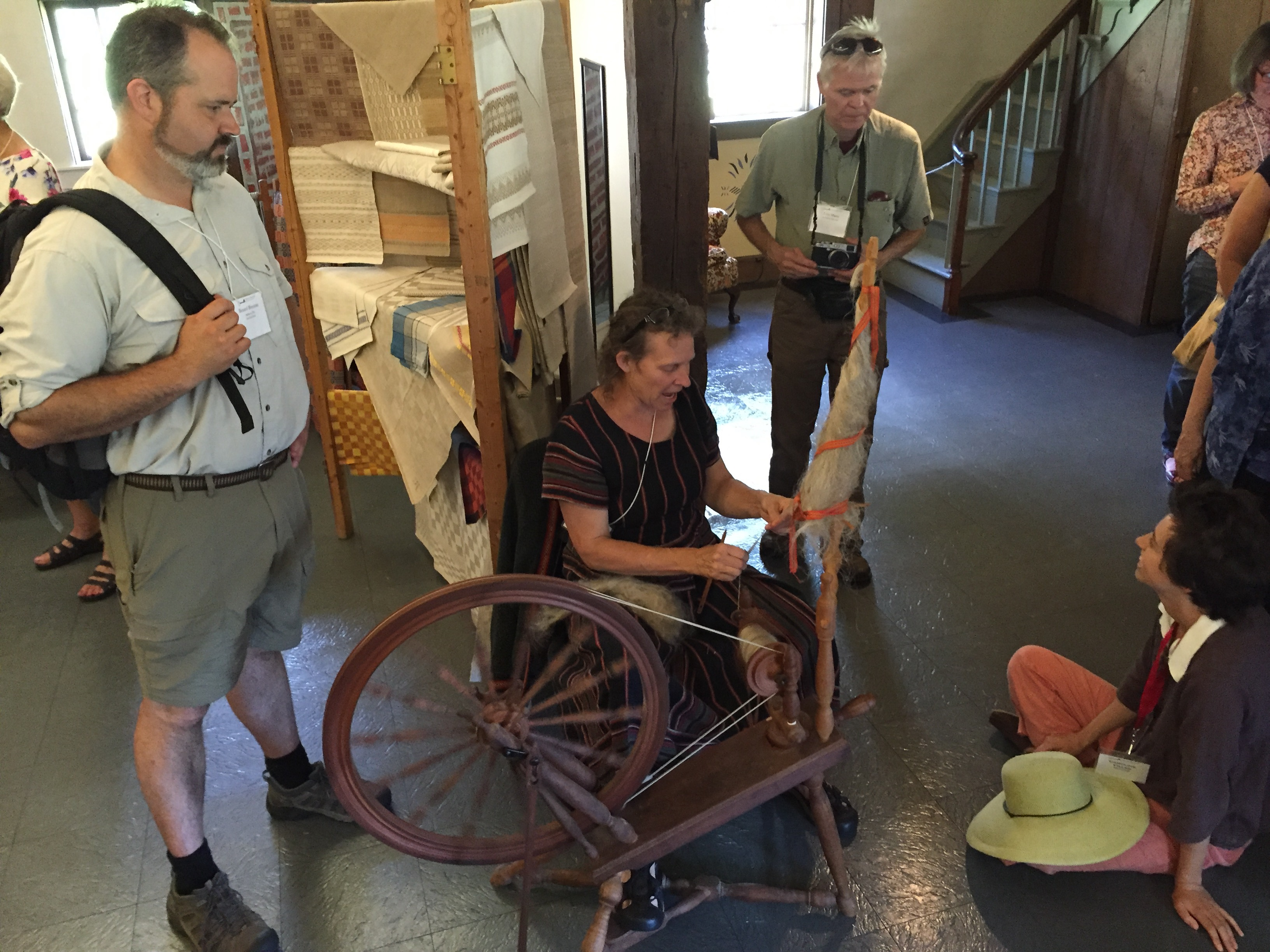 Photo of Becky Ashenden (seated) demonstrating spinning flax at the Flax & Linen Symposium 2016
