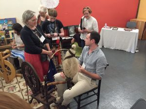 Photo of Justin Squizzero (seated) demonstrating spinning flax at the Flax & Linen Symposium 2016