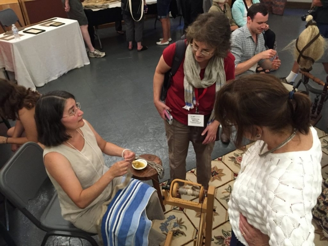 Photo of Chris Hammel (left) demonstrating spinning flax at the Flax & Linen Symposium 2016