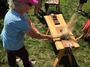 Photo of participant using a hetchel (or hackle) at the Flax & Linen Symposium 2016